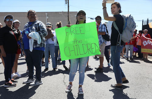 "Woman wearing ripped blue jeans and a baseball cap stands with a group of people on the street as she holds a green sign that says, ""Free the children."""