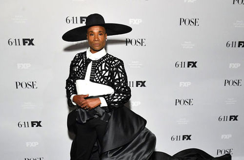 Billy Porter. Black man in white-brimmed black hat in black and white outfit.