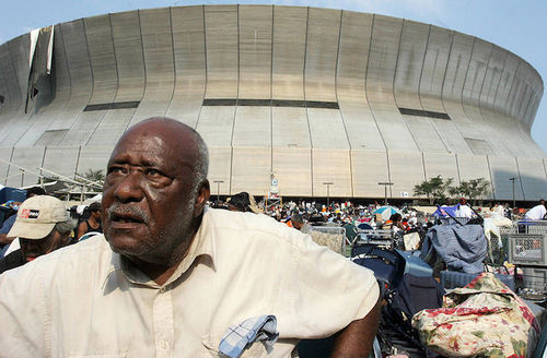 Black man stands outside of New Orleans Superdome after Hurricane Katrina