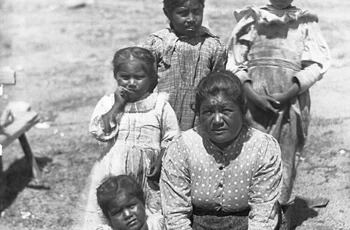 Black and white photo of Native American woman with four children, outside