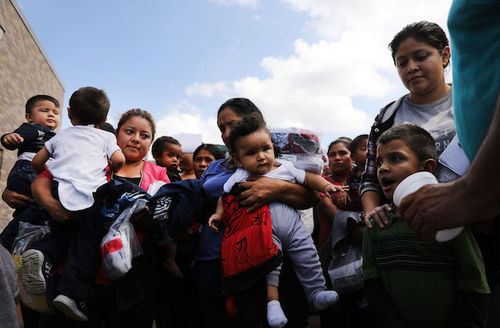 Women stand outside in a semicircle while holding their small children.