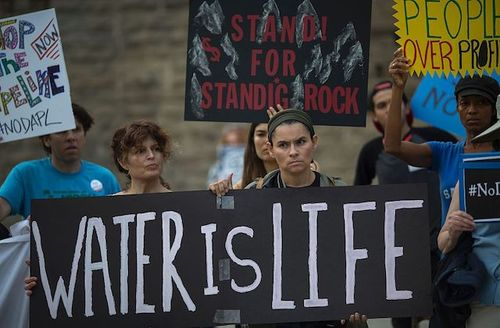 protestors hold signs against the Dakota Access pipeline
