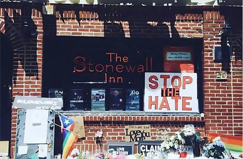 """Stonewall Inn. Many signs posted out front, including one reading  """"Stop the Hate."""""""