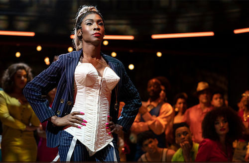 Angelica Ross. Black woman in character as Candy, wearing high ponytail, white corset, blue pin stripe jacket.