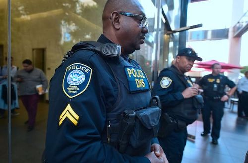 Profile image of Black male Department of Homeland Security agent wearing a police uniform and eyeglasses.