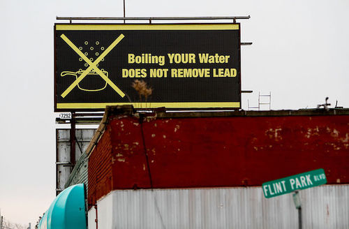 """Black and yellow billboard in Flint, Michigan, reads, """"Boiling your water does not remove lead."""""""