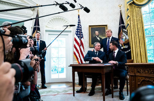 Politicians sit and shake hands as Trump stand over them inside the Oval Office of The White House.