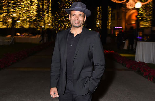 Mario Van Peebles. Middle-aged Black man wearing black hat and black suit and black shirt.