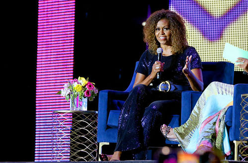 Michelle Obama. Black woman with natural brown curls wearing sequin jumpsuit.