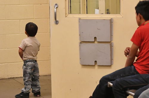 Two young boys wth black hair have their backs to camera inside a drab, cinderblock facility.