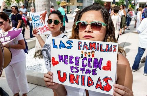 "Woman holds colorful protest sign that reads, ""families belong together"" in Spanish"