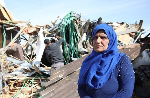 A Palestinian woman in a blue hijab stands before the ruins of her home.