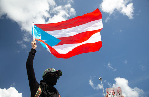 a masked man holding a Puerto Rican flag against a blue sky