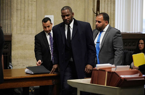 R. Kelly. Black man with short hair in courtroom, wearing dark suit, dark tie and white shirt.