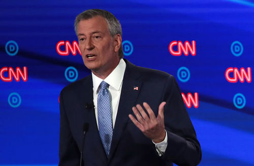 Bill de Blasio. White middle-aged man with short gray hair wearing dark suit, white shirt, and red tie on stage.