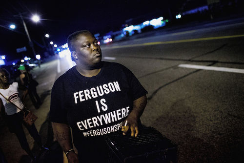 """A Black man wearing a t-shirt that says """"Ferguson is everywhere"""" protests at night."""