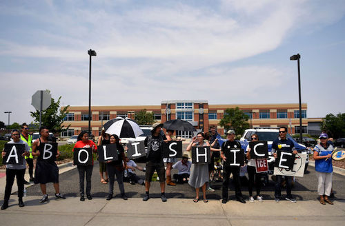 """Protestors hold black and white sign that reads """"Abolish ICE."""""""