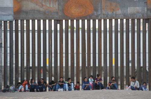 Large group of people sit in a straight line on the ground in front of a large southern border fence.