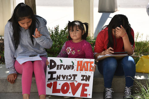 """A young Brown girl sitting between two older Brown girls holds up a sign that says, """"Defund Hate. Invest in Love"""""""
