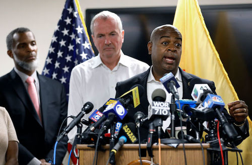 Newark Mayor Ras Baraka and Governor Philip D. Murphy at podium in Newark, New Jersey. American and yellow New Jersey flags in the background.