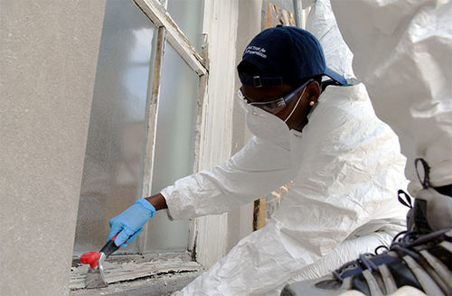 """""""Touching History."""" Black person dressed in white protective gear works on the floor restoring a window."""