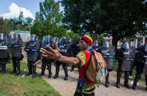 Black man wearing brightly colored daishiki holds his arms out as he stands before a large group of police officers wearing riot gear.