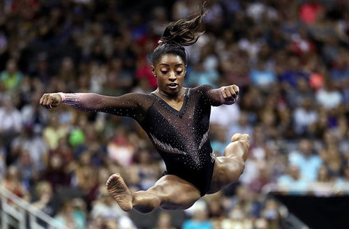 Simone Biles. Black person waring jeweled black leotard soars through the air, legs extended.