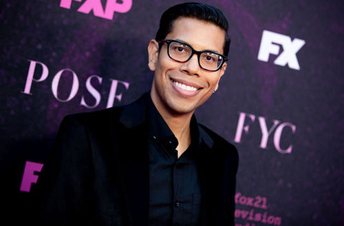 Steven Canals. Latinx man wearing dark glasses with dark hair, dresses in black suit jacket and black shirt.