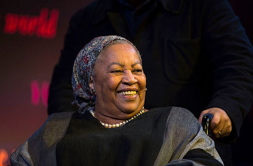 Toni Morrison. Older Black woman wearing gray headscarf and gray and black top.