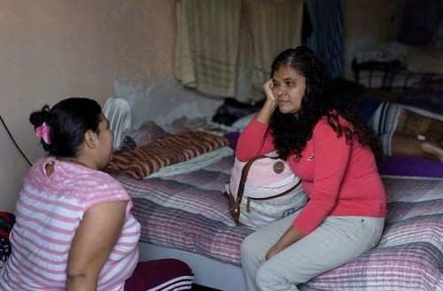 Two women in pink tops sit on beds facing each other as they speak.
