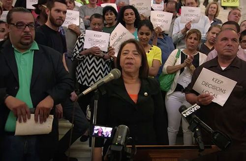 Carmen Castillo. Latinx woman standing in front of microphone surrounded by people.