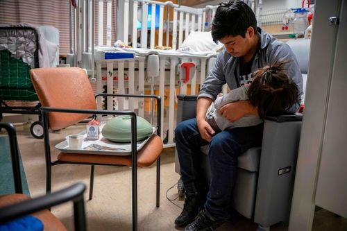 A man with dark hair sits in a chair holding his young daughter across his lap inside of her hospital room.