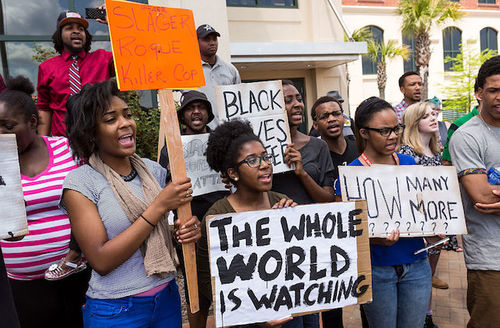 A group of Black women and men hold signs protesting the death of death of Walter Scott, who was killed by police in a shooting, outside City Hall in North Charleston, South Carolina, on April 8, 2015.