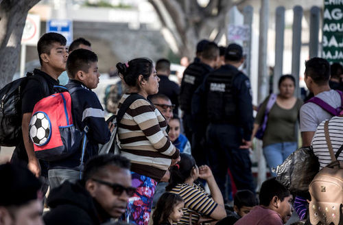 Large group of people stand with backpacks on their backs as they wait for their chance to claim asylum in the United States.