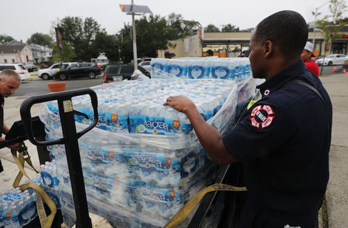 Fire department official stands with cases of bottled water in Newark, New Jersey