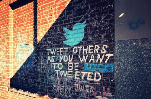 "Brick wall with chalk sign that reads, ""Tweet others as you want to be tweeted"" with a blue bird."