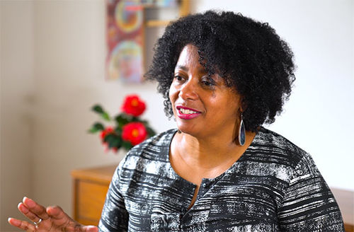 Jacqueline Olive, Black woman with Afro wearing black and white graphic top.