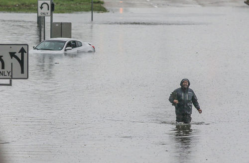 Person walks through flooded streets of Houston after Tropical Storm Imelda