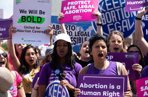 women in support of abortion rights holding pink, purple and white protest signs on Capitol Hill
