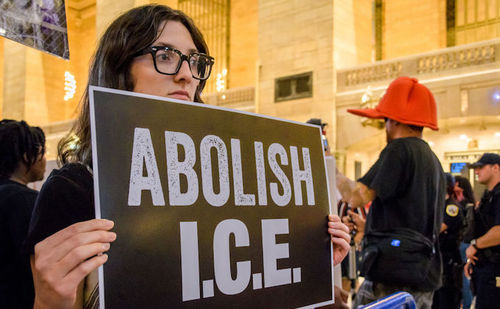 Woman with dark hair holds sign that says Abolish I.C.E.