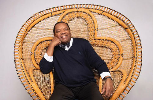 John Witherspoon. Older Black man sitting in peacock chair wearing dark sweater, white shirt, dark bow tie.