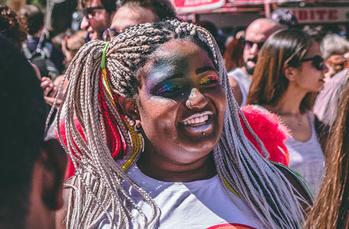 Young Black person with long braids and rainbow glitter face makeup.