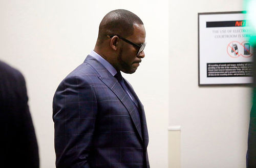 R.Kelly. Black man with short hair wearing dark gray suit.