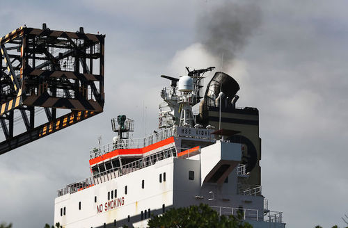 smoke being released from smoke stack on a container ship