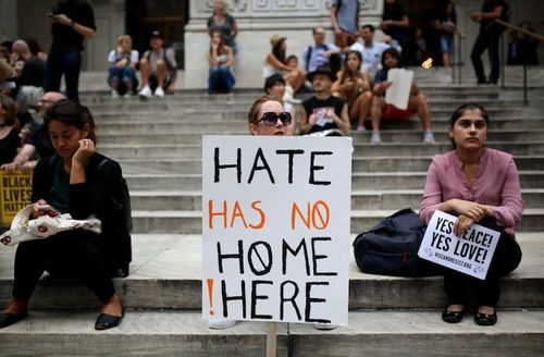 """Protester hold sign that reads """"hate has no home here"""""""