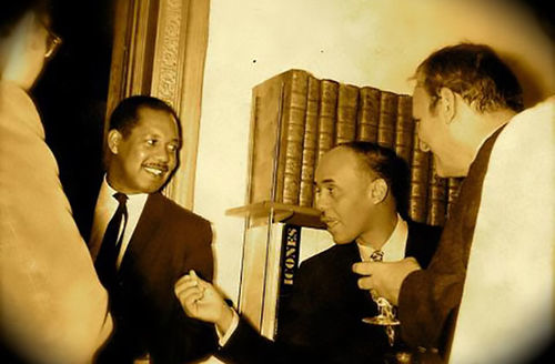 Ernest J. Gaines and Ralph Ellison. Two Black men wearing dark suits in conversation surrounded by White men.