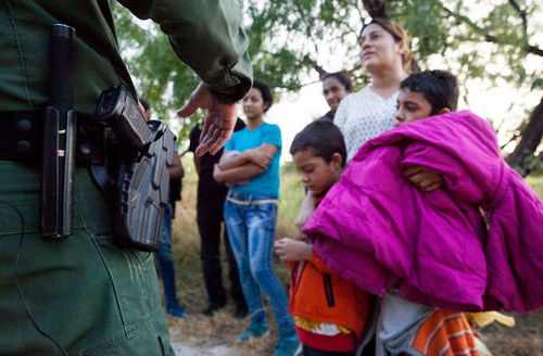 Small children and their mothers stand in front of an officer who has a gun in his holster