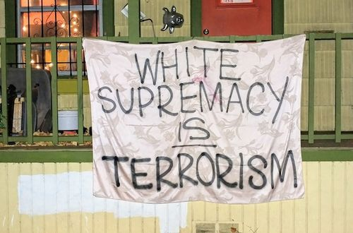 "A white sheet with the words ""White supremacy is terrorism"" written on it hangs on the front gate of a house"