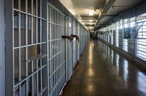 View of a long hallway inside a prison. A person's arms can be seen hanging through prison bars.