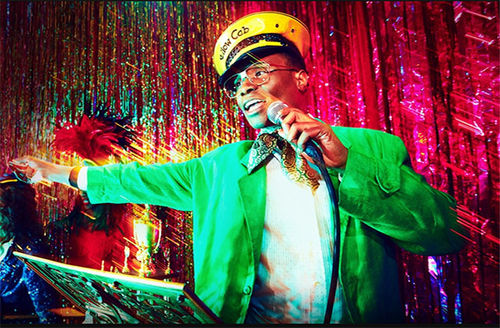 Billy Porter. Black man wearing yellow and black hat and green jacket.
